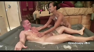 Cute oriental girl sucks dig up added to plays nearby soap all over be transferred to water-closet